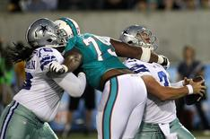Miami Dolphins Derrick Shelby (79) grabs Dallas Cowboys quarterback Nick Stephens (R) around the neck for a sack as he is blocked by Cowboys Edawn Coughman (L) during the first quarter of the NFL Hall of Fame Game in Canton, Ohio August 4, 2013. REUTERS/Aaron Josefczk
