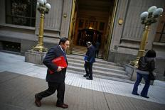 Personas caminan frente a la sede del Banco Central de Chile en el centro de Santiago. Imagen de archivo, 25 agosto, 2014. La inflación en Chile habría alcanzado un 0,7 por ciento en septiembre por alzas en alimentos, vestuario y los efectos de la depreciación del peso en importaciones clave, pese a la mayor desaceleración que enfrenta la economía, reveló el lunes un sondeo de Reuters. REUTERS/Ivan Alvarado