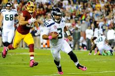 Oct 6, 2014; Landover, MD, USA; Seattle Seahawks quarterback Russell Wilson (3) runs with the ball as Washington Redskins outside linebacker Ryan Kerrigan (91) chases in the first quarter at FedEx Field. Mandatory Credit: Brad Mills-USA TODAY Sports