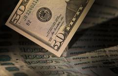 Купюры валют доллар США и рубль в Москве 17 февраля 2014 года. Рубль во вторник умеренно дешевеет из-за локального дефицита валюты в условиях ограничения доступа к зарубежным ресурсам и на фоне падения нефтяных цен, что происходит в русле текущих неблагоприятных тенденций глобальных рынков после снижения прогноза роста мировой экономики МВФ. REUTERS/Maxim Shemetov