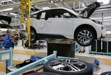 Una empleada monta una rueda en un vehículo eléctrico i3 en la planta de BMW en Leipzig, Alemania, sep 18 2013. Lo último que necesitaría la vacilante economía europea sería una repentina baja de la actividad en Alemania, el pilar en que se apoya del bloque.  REUTERS/Fabrizio Bensch