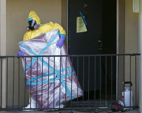 A worker in a hazardous material suit removes the contents of the apartment unit where a man diagnosed with the Ebola virus was staying in Dallas, Texas, October 6, 2014. REUTERS-Jim Young