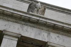 Орел на здании ФРС США в Вашингтоне 31 июля 2013 года. Регуляторы ФРС хотят связать повышение ключевой ставки с экономическим прогрессом США, но протокол их последнего заседания показывает, что они не знают, как справиться с двойной угрозой - сильным долларом и мировым спадом. REUTERS/Jonathan Ernst