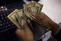 Un cajero cuenta dinero en Macy's Herald Square en Nueva York. Imagen de archivo, 28 noviembre, 2013. Las bolsas de Asia subían y el dólar retrocedía el jueves después de que las minutas de la última reunión de política monetaria de la Reserva Federal de Estados Unidos revelaron una preocupación de los funcionarios ante el fortalecimiento del dólar y el debilitamiento de la economía global. REUTERS/Eric Thayer