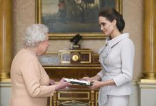 Atriz Angelina Jolie recebe honraria de Dama Honorária das mãos da rainha britânica Elizabeth, no palácio de Buckingham, em Londres. 10/10/2014.  REUTERS/Anthony Devlin/pool