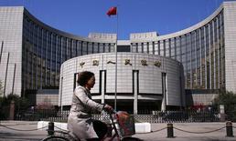 En la imagen de archivo, una mujer pasa en bicicleta frente a la sede del Banco Popular de China (PBOC), el banco central chino, en Pekín el 3 de abril del 2014. Las probabilidades de una fuerte desaceleración de la economía china es muy baja, pese a las preocupaciones sobre el sector inmobiliario del país, dijo el sábado el economista jefe del Banco Popular de China. REUTERS/Petar Kujundzic (CHINA - Tags: BUSINESS) - RTR3JVYR