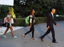 U.S. President Barack Obama and his daughters, Malia (C) and Sasha (L), depart the White House for the presidential retreat Camp David in Maryland, September 19, 2014. REUTERS/Larry Downing