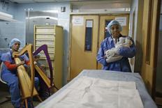 """Membros do programa """"O Sistema"""" tocam arpa durante o nascimento de um bebê em um hospital de Caracas, na Venezuela, no início de outubro. 01/10/2014 REUTERS/Carlos Garcia Rawlins"""