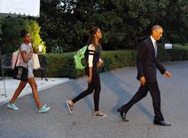President Obama and his daughters, Malia (C) and Sasha (L), depart the White House for the presidential retreat Camp David in Maryland, September 19, 2014. REUTERS/Larry Downing