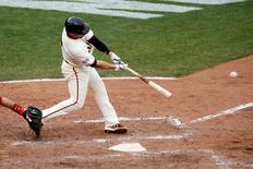 Oct 14, 2014; San Francisco, CA, USA; San Francisco Giants left fielder Juan Perez (2) hits a single during the tenth inning against the St. Louis Cardinals in game three of the 2014 NLCS playoff baseball game at AT&T Park. Mandatory Credit: Kelley L Cox-USA TODAY Sports
