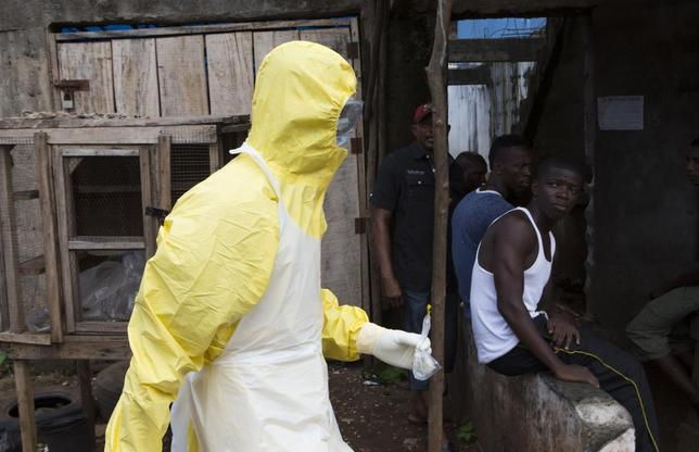 A health worker in protective equipment carries a sample taken from the body of someone who is suspected to have died from Ebola virus, near Rokupa Hospital, Freetown October 6, 2014. REUTERS/Christopher Black/WHO/Handout via Reuters