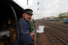 A train engineer looks out of a historic steam locomotive as it pulls a Tehran-bound train into Nyugati Terminus in Budapest, October 15, 2014.  REUTERS/Laszlo Balogh