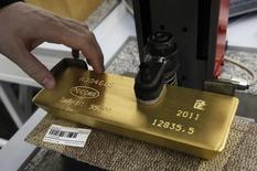 Автомат наносит гравировку на слиток золота в Красноярске 28 марта 2011 года. Крупнейший производитель золота в РФ Полюс Золото увеличил продажи золота в третьем квартале 2014 года на 14 процентов по сравнению со вторым до $603 миллионов, сообщила компания в четверг. REUTERS/Ilya Naymushin