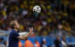 U.S. coach Juergen Klinsmann tosses the ball into the air it rolls over the line for a throw in during their 2014 World Cup round of 16 game against Belgium at the Fonte Nova arena in Salvador July 1, 2014. REUTERS/Marcos Brindicci