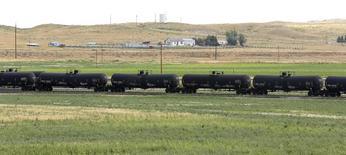 Цистерны с нефтью на терминале  Eighty-Eight Oil LLC в Вайоминге 15 июля 2014 года. Цены на нефть выросли почти на $1, поскольку инвесторы возвращаются на рынок, который они считают перепроданным. REUTERS/Rick Wilking