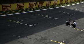 Funcionários da Pirelli inspecionam asfalto do circuito de Interlagos, em São Paulo. 24/11/2013 REUTERS/Nacho Doce