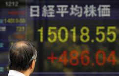 Un hombre observa una pantalla que muestra el índice Nikkei en Tokio, 20 octubre, 2014. Las acciones japonesas lideraban un repunte en Asia el lunes, luego de que unos sólidas datos y ganancias corporativas desde Estados Unidos calmaron la agitación en los mercados financieros mundiales y tranquilizaron a los inversores preocupados por la salud de la economía mundial. REUTERS/Yuya Shino