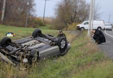 A Surete du Quebec (SQ) officer investigates an overturned vehicle in Saint-Jean-sur-Richelieu, Quebec October 20, 2014. REUTERS/Christinne Muschi