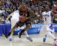 Cincinnati Bearcats' Sean Kilpatrick (23) drives past Creighton Bluejays' Austin Chatman (1) during the first half of their second round NCAA tournament game in Philadelphia, Pennsylvania, March 22, 2013. REUTERS/Tim Shaffer