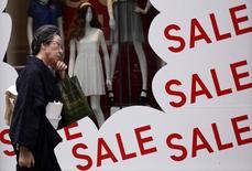 Женщина проходит мимо витрины магазина с объявлением о скидках в Токио 26 июня 2014 года. Правительство Японии сократило оценку экономики второй месяц подряд, так как низкие потребительские расходы после повышения налога с продаж в апреле заставляют компании сокращать производство. REUTERS/Yuya Shino