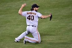 Oct 21, 2014; Kansas City, MO, USA; San Francisco Giants starting pitcher Madison Bumgarner throws to first base after catching a ball hit by Kansas City Royals first baseman Eric Hosmer (not pictured) in the 6th inning during game one of the 2014 World Series at Kauffman Stadium. Peter G. Aiken-USA TODAY Sports