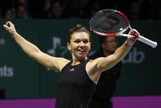 Simona Halep of Romania celebrates her win over Serena Williams of the U.S. during their WTA Finals singles tennis match at the Singapore Indoor Stadium October 22, 2014. REUTERS/Edgar Su