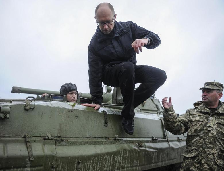 Ukrainian Prime Minister Arseny Yatseniuk jumps off an armored personnel carrier (APC) during a visit to the International Center of Peacekeeping and Security in Yavoriv, west of Lviv, October 21, 2014. REUTERS/Andrew Kravchenko/Pool