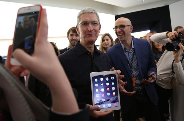Apple CEO Tim Cook holds a new iPad after a presentation at Apple headquarters in Cupertino, California October 16, 2014.  REUTERS/Robert Galbraith