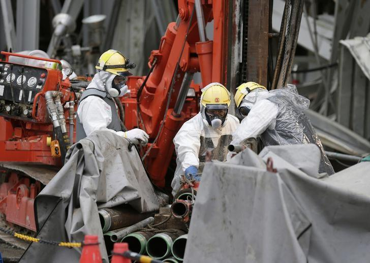 Workers conduct operations to construct an underground ice wall at Tokyo Electric Power Co.'s (Tepco) tsunami-crippled Fukushima Daiichi nuclear power plant in Fukushima Prefecture July 9, 2014. REUTERS/Kimimasa Mayama/Pool