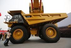 Мужчина смотрит на трак Caterpillar на выставке  China Coal and Mining Expo 2013 в Пекине 22 октября 2013 года. Квартальная прибыль Caterpillar Inc превзошла ожидания аналитиков, и компания повысила прогноз на 2014 год, благодаря чему ее акции выросли более чем на 5 процентов в четверг. REUTERS/Kim Kyung-Hoon