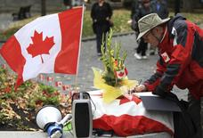 A man writes in books of condolences to fallen Canadian soldiers, Warrant Officer Patrice Vincent and Corporal Nathan Cirillo, during a vigil in Montreal, October 25, 2014.  REUTERS/Christinne Muschi