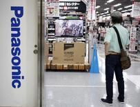 A man stands next to a logo of Panasonic Corp inside an electronics retail store in Tokyo July 31, 2014. REUTERS/Yuya Shino