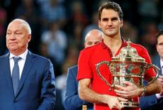 Tournament director Roger Brennwald (L) stands beside as Switzerland's Roger Federer holds the trophy after winning his final match against Belgium's David Goffin at the Swiss Indoors ATP tennis tournament in Basel October 26, 2014.   REUTERS/Arnd Wiegmann