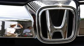 Man are reflected on a Honda Motor car outside the company showroom in Tokyo July 29, 2014.   REUTERS/Toru Hanai