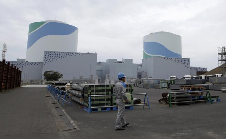 An employee of Kyushu Electric Power Co walks in front of reactor buildings at the company's Sendai nuclear power plant in Satsumasendai, Kagoshima prefecture April 3, 2014.  REUTERS/Mari Saito/Files