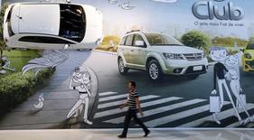 Um homem passa em frente a cartaz da Fiat no Salão Internacional de Automóveis em São Paulo 28/10/ 2014. REUTERS/Paulo Whitaker