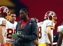 Oct 12, 2014; Glendale, AZ, USA; Washington Redskins injured quarterback Robert Griffin III (left) reacts behind quarterback Kirk Cousins on the sidelines in the fourth quarter against the Arizona Cardinals at University of Phoenix Stadium. The Cardinals defeated the Redskins 30-20. Mandatory Credit: Mark J. Rebilas-USA TODAY Sports