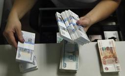 Сотрудник банка пересчитывает купюры в Москве 2 сентября 2014 года. Банк России повысил ключевую ставку на 150 базисных пунктов до 9,50 процента годовых, что стало неожиданностью для большинства аналитиков. REUTERS/Maxim Zmeyev