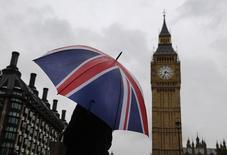 Una mujer sujeta un paraguas con la bandera de Gran Bretaña frente a la torre del Big Ben en Londres. Imagen de archivo, 04 octubre, 2014. Gran Bretaña liquidará el próximo año parte de la deuda pendiente que se contrajo para financiar la Primera Guerra Mundial, cuando rescate bonos del Gobierno emitidos por primera vez hace casi 90 años por el entonces ministro de Finanzas Winston Churchill. REUTERS/Luke MacGregor
