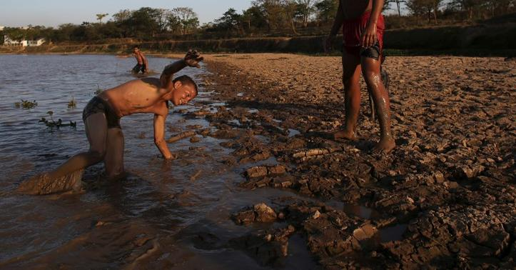 Natalino Pereira (L), 12, and Orlando Fernandez, 15, joke next to the cracked ground of the Itaim dam as the eight-month rationing of water continues as a result of a record drought, in Itu, October 28, 2014.  REUTERS-Nacho Doce