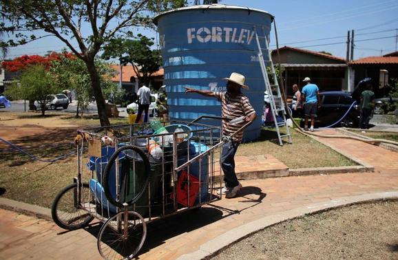 A resident of the region of Sao Paulo state that depends on the Cantareira water system, pushes a cart with containers to fill from a water tank as the eight-month rationing of water continues as a result of a record drought, in Itu, October 28, 2014.  REUTERS-Nacho Doce