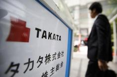 A man walks past a sign board of Japanese auto parts maker Takata Corp's Annual General Meeting in Tokyo June 26, 2014. REUTERS/Yuya Shino/Files