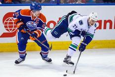 Nov 1, 2014; Edmonton, Alberta, CAN; Edmonton Oilers defenseman Andrew Ference (21) and Vancouver Canucks center Shawn Matthias (27) battle for the puck during the third period at Rexall Place. Vancouver Canucks won 3-2. Mandatory Credit: Sergei Belski-USA TODAY Sports