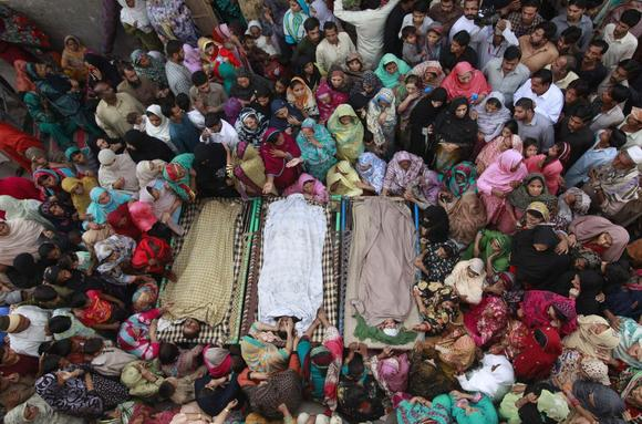 Relatives gather beside the bodies of victims who were killed in yesterday's suicide bomb attack on the Wagah border, before funeral prayers in Lahore, Pakistan, November 3, 2014.