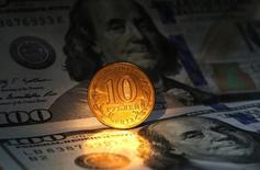 Долларовые купюры и 10-рублевая монета в Санкт-Петербурге 22 октября 2014 года. Рубль резко подешевел на торгах среды после решения Центробанка отменить нелимитированные интервенции, ограничившись $350 миллионами в день, но с возможностью дополнительных продаж. REUTERS/Alexander Demianchuk
