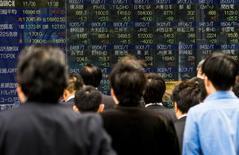 Пешеходы у брокерской конторы в Токио 6 ноября 2014 года. Азиатские фондовые рынки завершили торги четверга разнонаправленно под влиянием отдельных отраслей. REUTERS/Thomas Peter