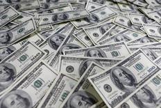 Долларовые купюры в банке в Сеуле 9 января 2013 года. Курс доллара к корзине шести основных валют близок к четырехлетнему максимуму накануне выхода отчета о занятости в США. REUTERS/Lee Jae-Won