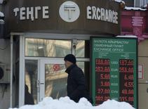 Мужчина у обменного пункта в Алма-Ате 11 февраля 2014 года. Казахстан в ближайшие три года не будет девальвировать тенге, рассчитывая на стабильность экономики и способность тенге противостоять значительным падениям курса рубля в России – главном торговом партнёре, повторил в пятницу регулятор. REUTERS/Vladimir Tretyakov