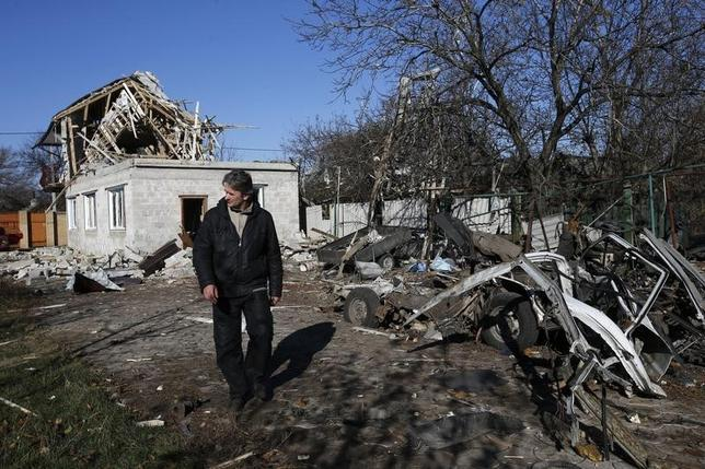 A man walks past a residential block and a car damaged by recent shelling in Donetsk, eastern Ukraine, November 6, 2014. REUTERS/Maxim Zmeyev
