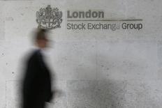 Мужчина проходит мимо вывески Лондонской фондовой биржи 11 октября 2013 года. Европейские фондовые рынки растут за счет акций голландского производителя кормов для животных Nutreco. REUTERS/Stefan Wermuth